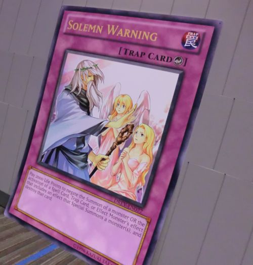 I need 3 Duelists to re-enact this scene this weekend, in front of this giant card. Send photos to us-ygorules@konami.com!